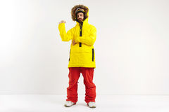 Snowboarder demonstrating bright anorak coat. Fashionable fit snowboarder in bright yellow coat and red pants pointing behind his back while looking into the Stock Photo