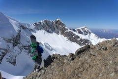Snowboarder, der auf einen Berg steht Lizenzfreie Stockbilder