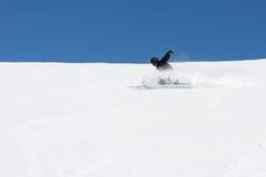Snowboarder, der eine Drehung an einem Tag des blauen Himmels schnitzt Lizenzfreie Stockfotos
