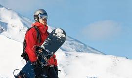 Snowboarder, der einen Snowboard hält lizenzfreies stockbild