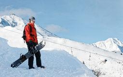 Snowboarder, der einen Snowboard hält stockfotografie