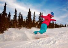 Snowboarder, der hinunter den Hügel schiebt Lizenzfreie Stockbilder