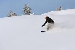 Snowboarder, der hinunter den Hügel schiebt Stockfoto