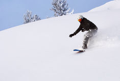 Snowboarder, der hinunter den Hügel schiebt Lizenzfreies Stockfoto
