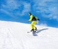 Snowboarder, der hinunter den Hügel, Schneeberge schiebt Stockfoto