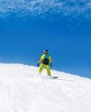 Snowboarder, der hinunter Hügel, Schneesnowboarding schiebt Stockfoto