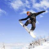 Snowboarder, der Hochsprung über dem Berg tut Stockfotos