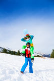 Snowboarder, der Mädchen auf seinen Schultern hält Lizenzfreie Stockfotografie