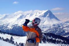 Snowboarder, der Mineralwasser trinkt Lizenzfreies Stockfoto
