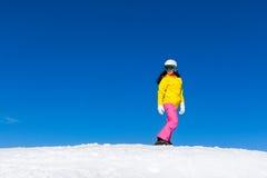 Snowboarder, der unten Hügel der Frau, Schnee schiebt Stockfoto