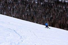 Snowboarder des jungen Mädchens in der Bewegung auf Snowboard in den Bergen Lizenzfreie Stockfotografie
