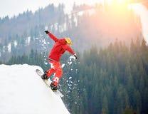 Snowboarder des jungen Mannes, der von der Spitze des schneebedeckten Hügels mit Snowboard am Abend springt Stockfoto