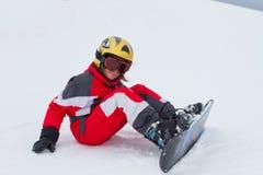 Snowboarder des kleinen Mädchens, der an der Skisteigung in den französischen Alpen sitzt Lizenzfreie Stockbilder