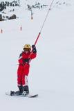 Snowboarder des kleinen Mädchens steigt oben am Skischleppseil in den französischen Alpen Stockbilder
