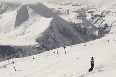 Snowboarder descend on snowy ski slope and gondola lift. At winter day. Georgia, region Gudauri. Caucasus Mountains. Black and white toned landscape stock photography