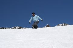 Snowboarder descends a slope Stock Image