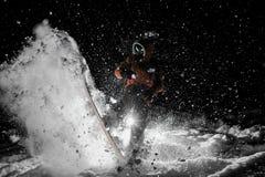 Snowboarder di Freeride che salta sul bordo in neve alla notte fotografie stock