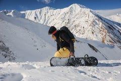 Snowboarder di Freeride che tiene un bordo sui precedenti delle montagne fotografie stock