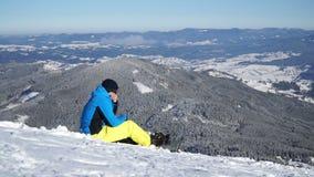 Snowboarder die bovenop een berg rusten stock videobeelden
