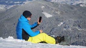 Snowboarder die de telefoon uitnodigen die op de bovenkant van de helling rusten stock footage