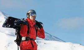 Snowboarder die een snowboard houden Stock Fotografie