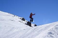 Snowboarder die in sneeuwpark bij skitoevlucht springt op de dag van de zonwinter Royalty-vrije Stock Afbeelding