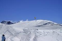 Snowboarder die in sneeuwpark bij skitoevlucht springt op de dag van de zonwinter Royalty-vrije Stock Foto