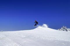 Snowboarder die in sneeuwpark bij skitoevlucht springt op de dag van de zonwinter Stock Foto's