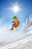 Snowboarder die tegen blauwe hemel springt Stock Fotografie