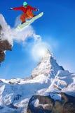 Snowboarder die tegen Matterhorn-piek in Zwitserland springen stock fotografie