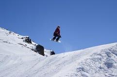 Snowboarder die in terreinpark bij skitoevlucht springen op de zonwinter Royalty-vrije Stock Foto's