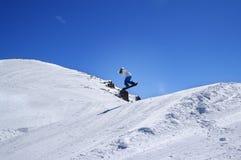 Snowboarder die in terreinpark bij skitoevlucht springen op de zonwinter Royalty-vrije Stock Fotografie