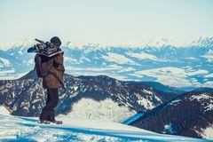 Snowboarder die zich bij de bovenkant van een berg bevinden en snowboard op zijn schouders met mooi landschap vóór hem houden stock afbeelding