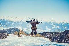 Snowboarder die zich bij zeer hoogste van een berg bevinden en snowboard op zijn schouders met mooi landschap vóór hem houden royalty-vrije stock afbeeldingen