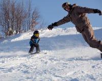 Snowboarder do homem e esquiador pequeno Fotos de Stock Royalty Free