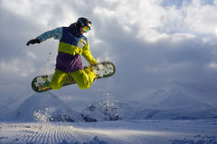 Snowboarder does the jumping trick. snow scatters pieces Stock Photography