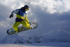 Snowboarder doet de springende truc de sneeuw verspreidt stukken Stock Foto's