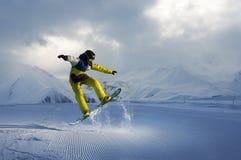 Snowboarder doet de springende truc de sneeuw verspreidt stukken Stock Afbeeldingen