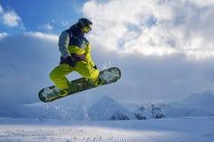 Snowboarder doet de springende truc de sneeuw verspreidt stukken Stock Afbeelding