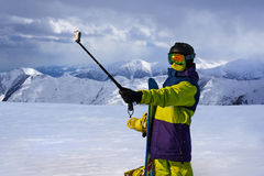 Snowboarder doing selfie on action camera    stick Stock Photos