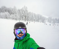 Snowboarder doing selfie on camera Royalty Free Stock Images