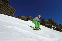 Snowboarder doing a toe side carve with deep blue sky in backgro Stock Image