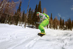 Snowboarder doing a toe side carve with deep blue sky in backgro Royalty Free Stock Photography