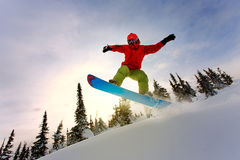 Snowboarder doing a toe side carve with deep blue sky in backgro Stock Photography