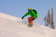 Snowboarder doing a toe side carve with deep blue sky in backgro Stock Photo