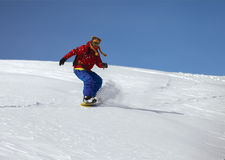 Snowboarder doing a toe side carve with deep blue sky in backgro Royalty Free Stock Photos