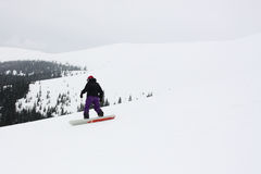 Snowboarder down the snowy slope Royalty Free Stock Images