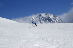 Snowboarder downhill in high snowy mountains Royalty Free Stock Photos