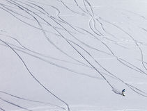 Snowboarder downhill on off piste slope with newly-fallen snow Royalty Free Stock Photography