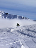 Snowboarder downhill on off-piste slope in sunny day Stock Photo